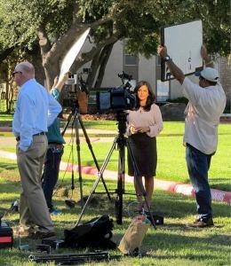 Une journaliste magnifiée devant les caméras de télévision.