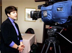Une femme est intervieweée devant une caméra de télévision.